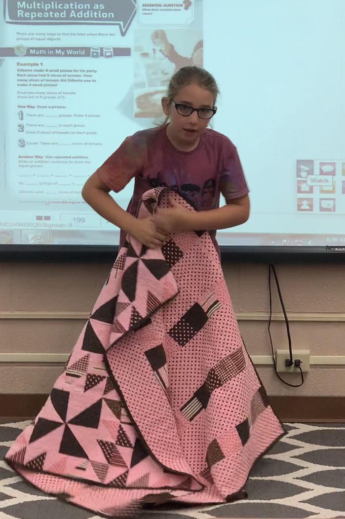 Student holding quilt